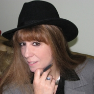 Close up photo of author Mae Clair, who is wearing black fedora hat and hold pen