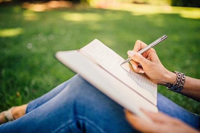 writing in a journal on the lawn